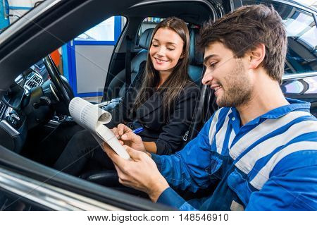 Car mechanic with female customer going through maintenance checklist in automobile shop