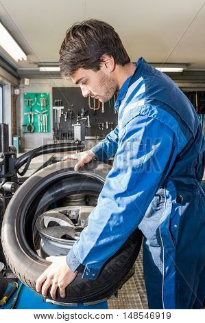 Side view of male mechanic mounting car tire on alloy rim in garage