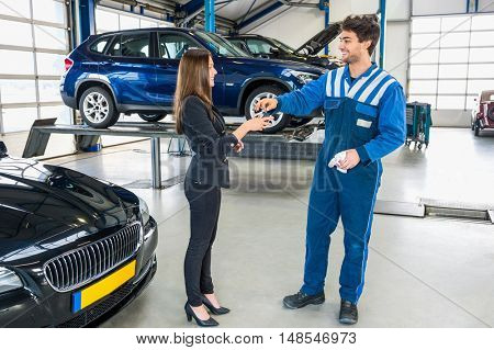 Full length of young mechanic giving car key to client after servicing at garage