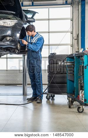 Full length of male mechanic repairing brake of lifted automobile at garage