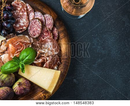 Italian antipasti snack for wine. Prosciutto di Parma, salami, cheese variety, figs, grapes, peach, walnuts and fresh basil on wooden serving tray with glass of Rose, dark grunge background. Top view, copy space