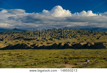 Tien Shan foothills illuminated with evening sun. Two car in foreground. Travel to Issyk Kul lake region.