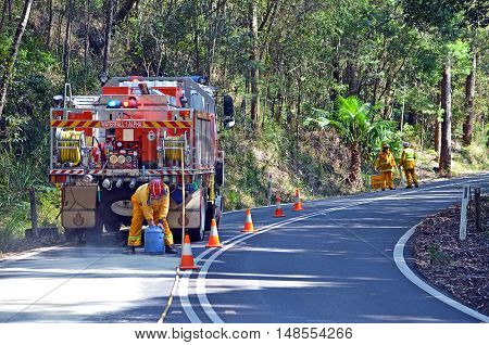 September 11, 2016. Waterfall fire brigade manage an oil spill from broken down tour bus engine in Royal National Park, Sydney, Australia. Road dangerous, slippery and closed for chemical clean up