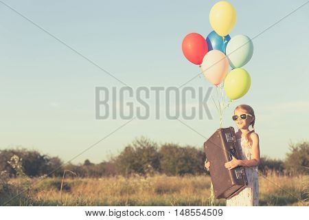 Happy little girl playing on road at the day time. She standing in the field and holding in hands suitcase and balloons. Kid having fun on the nature. Concept of happiness.