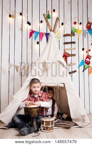 Kids playing drum sitting inside wigwam in decorated wooden room