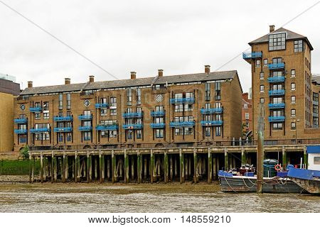 High-rise Riverside brick houses on the Thames river in St. Katharine area in London England.