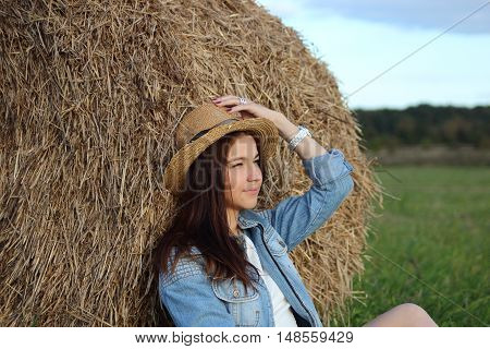 Girl on the field with hay and hat and glasses