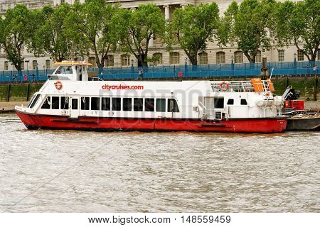 LONDON, ENGLAND - JULY 8, 2016: A City Cruises tour boat sails on the Thames river. Thames is the longest river in England with 346 km (215 miles) long.
