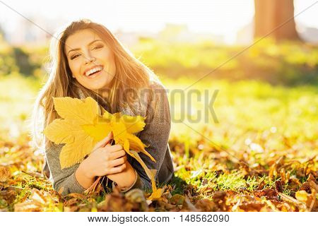 Beautiful happy young woman in park in fall holding leaves. Cheerful blonde teenage girl outdoors in autumn, lying on the ground. Vibrant colors, medium retouch.