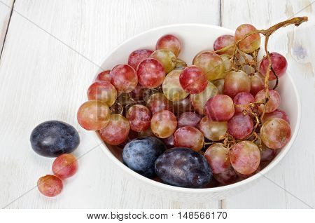 Plums And Grapes In Bowl On The White Wooden Table
