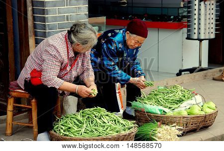 Luo Dai China - October 13 2007: Two Chinese women seated on bamboo stools on a sidewalk selling green beans and scallions displayed in baskets