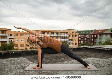Beautiful woman practicing yoga on the roof,Utthita Parsvokonasana /Extended right side angle pose