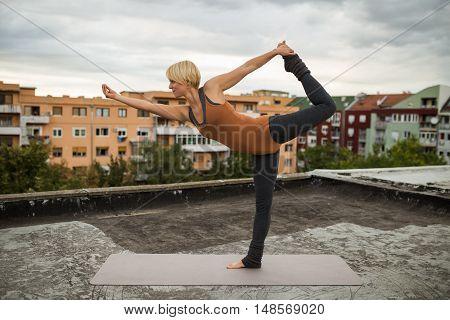 Beautiful woman practicing yoga on the roof,Natarajasana / Shiva posture poster
