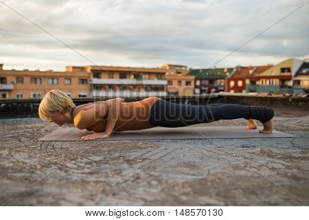 Woman practicing yoga on the roof,Chaturanga Dandasana/Four-Limbed Staff Pose