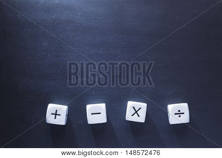 white math operator dices on blackboard good background for education concept with harsh lighting showing long dices' shadows and selective focus on dices room for copy space
