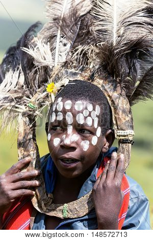 AFRICA, KENYA, MAY, 08, 2016 - African children with ostrich feather headdress  and painted markings of face at Masai Mara National Park, Kenya, Africa