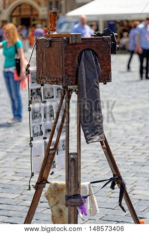 PRAGUE, CZECH REPUBLIC - JULY 3, 2014: Tourists are invited to take a picture by antique camera in the Old town square. Various artists show and sell their works at tourist hot spots in Prague.