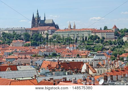 Aerial view of the traditional red roofs of the city of Prague Czech Republic with Prague castle Hradcany in the background.
