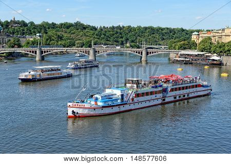 PRAGUE, CZECH REPUBLIC - JULY 3, 2014: View of the Vltava river with cruise tour boats from the Charles Bridge. The Charles Bridge is a famous historic bridge that crosses the Vltava river in Prague.