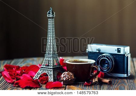 Love Paris Rose vintage camera Eiffel tower coffee cup chocolate red rose petals cinnamon sticks on wooden table St Valentine's Day concept Nostalgic holidays background card with place for your text