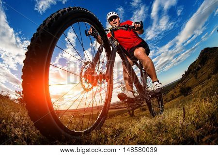 Cyclist Riding Mountain Bike On Rocky Trail At Sunrise