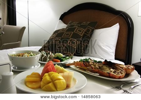 Room service food presentation with hotel bed in background served lobster