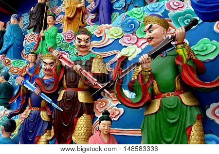 Mianyang China - October 15 2010: Three warriors on the hand-painted sculpture tableaux at the Sheng Shui Buddhist temple dating to the Tang and Qing Dynasties