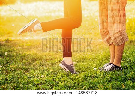 Legs of young couple standing in front of each other in park in autumn. Heterosexual couple, unrecognizable people, kissing, standing in grass on sunny day. Vibrant colors.