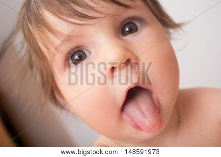 Cute baby showing tongue. close up portrait