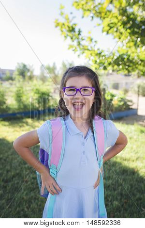 A girl wearing a uniform and a backpack is ready for her first day of school.