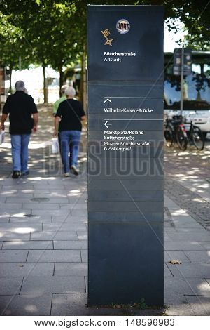 BREMEN, GERMANY - AUGUST 30: Walkers on a sidewalk with a sign and a signpost in front of the Old Town on August 30, 2016 in Bremen.