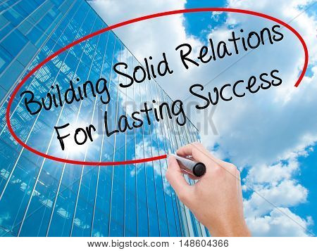 Man Hand Writing Building Solid Relations For Lasting Success With Black Marker On Visual Screen