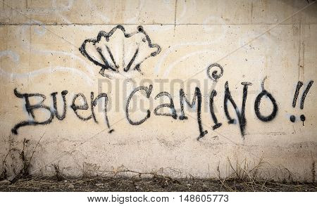 Buen Camino words and a shell painted on a wall on the way of Santiago