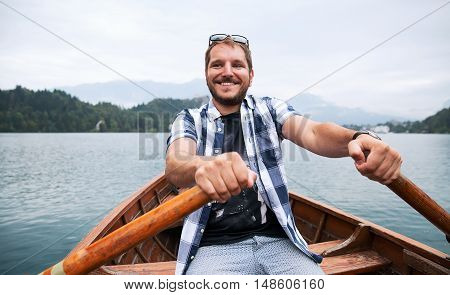 Tourist traveling by wooden boat among the forest islands with oars on lake with cloudy mountains and fog on background. Traditional wooden boat on the Lake Bled Slovenia. Autumn time in Europe.