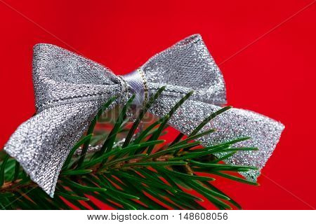 Christmas silvery bow with  fir branch at red backdrop