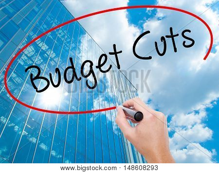 Man Hand Writing Budget Cuts With Black Marker On Visual Screen