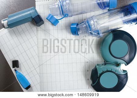 Asthma relief concept inhalers aerosol medication and paper on chrome background