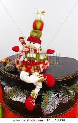 Funny snowman sits on vintage brouwn coffer with white christmas tree decoration copy space