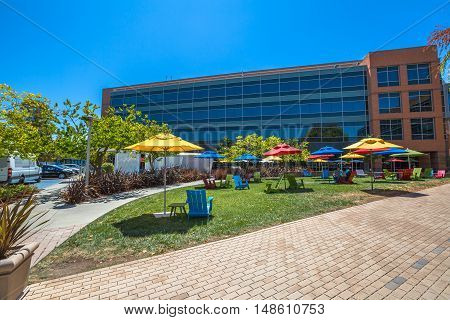 Mountain View, California, United States - August 15, 2016: dining and relaxing area with colorated parasols and deck chairs for sunbathing for Google employees at Google's headquarters or Googleplex.
