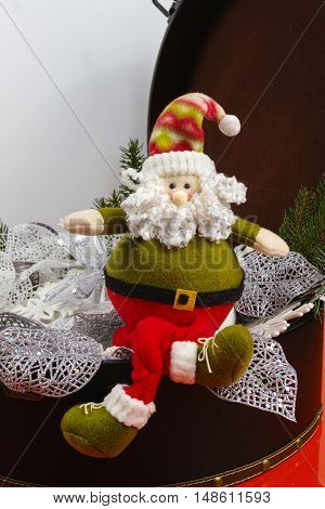 Santa Claus sits on vintage brouwn coffer with white christmas tree decoration copy space