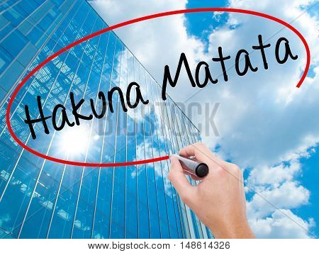 "Man Hand Writing Hakuna Matata (swahili Phrase; It Means ""no Worries"") With Black Marker O"