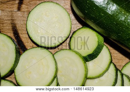 Fresh sliced summer squash zucchini.  Healthy organic nutritious and delicious vegetable.  Homegrown and prepared on a well worn cutting board.