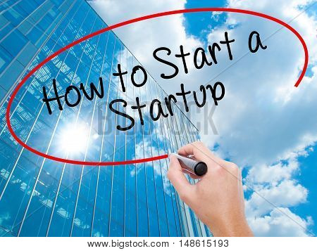Man Hand Writing How To Start A Startup With Black Marker On Visual Screen