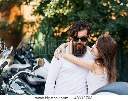Young couple of bearded hipster man and beautiful girl hug in love outdoor near motor bike