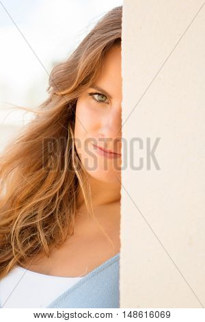 Portrait of a beautiful woman hidden behind a wall