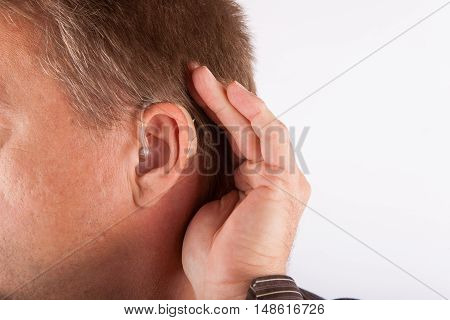 Close up ear of a man wearing hearing aid cupping his hand behind his ear