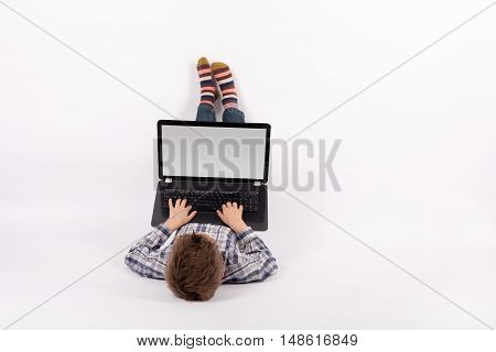 Young boy lying and using a laptop with empty screen suitable for text. Studio shot with white background.
