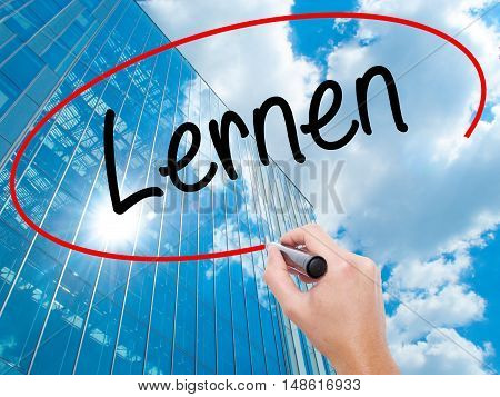 Man Hand Writing Lernen (learn In German) With Black Marker On Visual Screen.