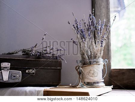 still life. vintage. old suitcase and sprigs of lavender on the background of old windows to the garden.