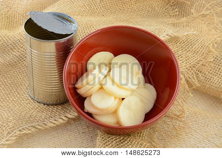 Canned rinsed sliced potatoes in red bowl with opened can